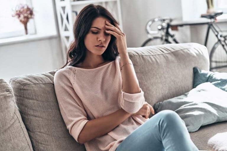 Eine junge Frau sitzt auf dem Sofa und hält sich die Hand an den Kopf